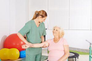 Alte Frau mit kranker Schulter zur Behandlung bei der Physiotherapie